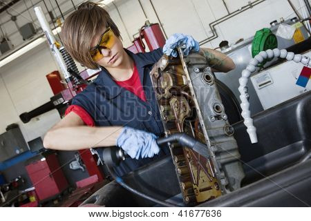 Young female mechanic working with welding torch on vehicle machinery part in auto repair shop