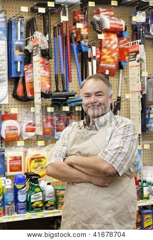 Portrait of a confident middle-aged salesperson with arms crossed in hardware store