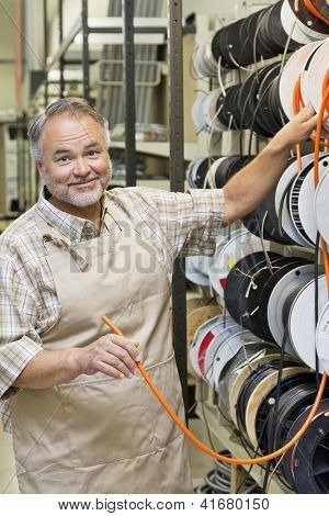 Portrait of a happy middle-aged store clerk with electrical wire spool in hardware shop