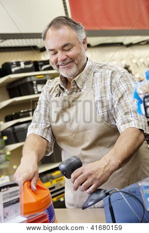 Happy middle-aged store clerk using bar code reader at checkout counter