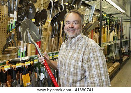 Retrato de un hombre de mediana edad feliz con pala en Ferreterias