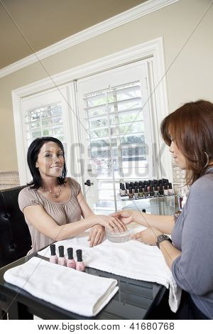 Young manicurist polishing nails of beautiful happy female