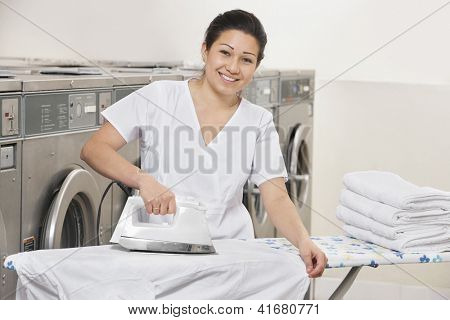 Portrait of a happy young woman ironing clothes in Laundromat