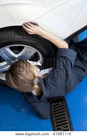 High angle view of young mechanic lying on floor working on car tire in garage