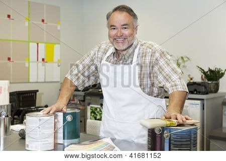 Portrait of a cheerful middle-aged sales clerk with paint can in hardware store