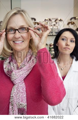 Portrait of a happy woman trying glasses with optician in background