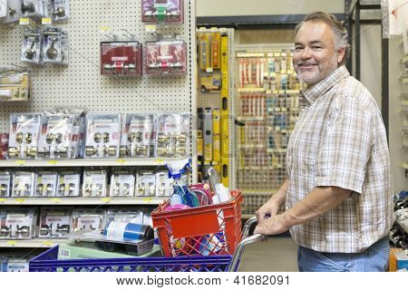 Side view portrait of a happy middle-aged man with shopping cart in hardware store