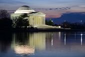 Thomas Jefferson Memorial silhouette at sunrise with mirror reflection on water, Washington DC Unite