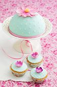 stock photo of sugarpaste  - Round cake and three cupcakes decorated with fondant and gum paste flowers - JPG