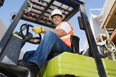 Low angle view of a confident male industrial worker driving forklift at workplace