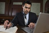 pic of courtroom  - Young male advocate using laptop while preparing notes in courtroom - JPG