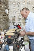 stock photo of locksmith  - Side view of senior locksmith making key in store - JPG