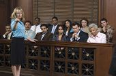 stock photo of jury  - Portrait of a female advocate pointing with jurors sitting together in the witness stand at court house - JPG