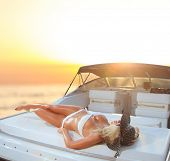 image of bimbo  - Young sexy woman in white bikini enjoying the sunset on her private yacht - JPG