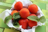 stock photo of regrouping  - some tomatoes with leaves in a basket - JPG