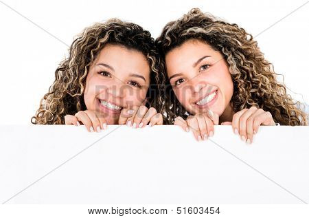 Happy twin sisters holding a banner - isolated over a white background