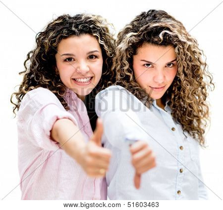 Twin sisters with thumbs up and down - Like or dislike concepts