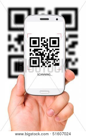 male hand is holding a modern touch screen phone and scanning QR code.