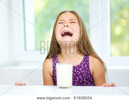 Sad little girl refuses to drink a glass of milk