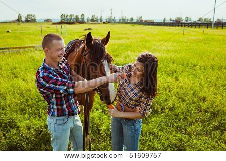 young couple feeding horse