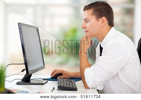 thoughtful young businessman looking at computer screen