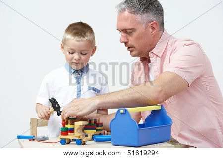 Teacher And Pre School Pupil Playing With Wooden Tools