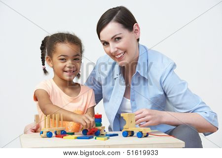 Teacher And Pre-School Pupil Playing With Wooden House