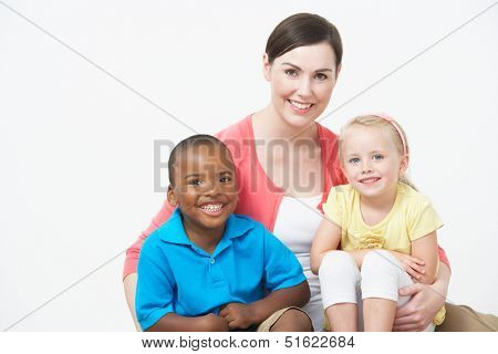 Studio Portrait Of Female Pre School Teacher With Pupils