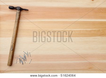 Hammer And Metal Panel Pins On A Woodgrain Background