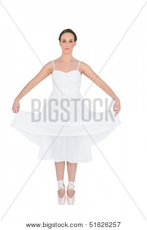 Peaceful young ballet dancer standing on her tiptoes on white background