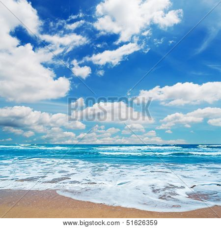 Frothy Shore And Scenic Clouds