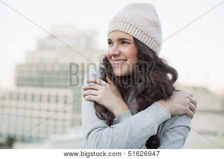 Smiling pretty young brunette shivering outside on a cloudy day