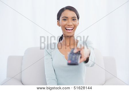 Smiling woman sitting on sofa in bright living room changing tv channel