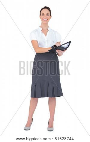 Smiling businesswoman holding her datebook on white background