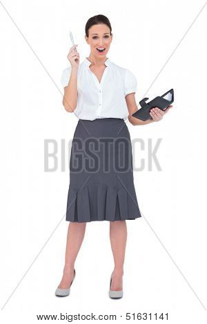 Surprised businesswoman holding her datebook on white background