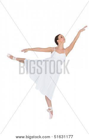 Focused ballet dancer posing on her tiptoe while rising a leg on white background