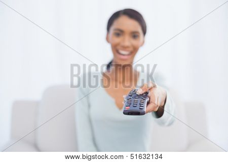 Cheerful woman sitting on sofa in bright living room changing tv channel