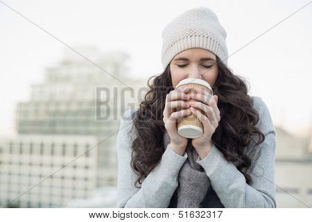Pretty young brunette drinking coffee outside on a cloudy day