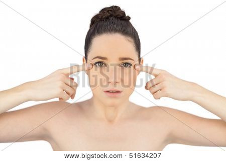Natural model showing crows feet on her eyes while posing on white background