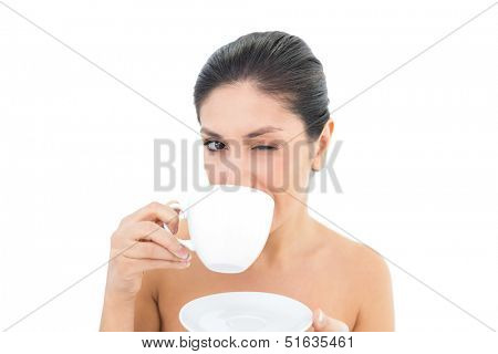 Pretty brunette holding a cup and saucer and taking a sip while winking on white background
