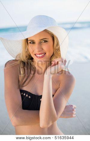 Cheerful sensual blonde in elegant black bikini wearing straw hat on a beautiful sunny beach