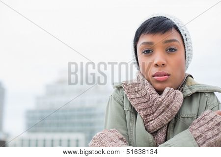 Cute young model in winter clothes shivering outside on a cloudy day