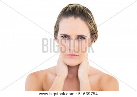 Disgruntled woman looking at camera with a sore neck against white background