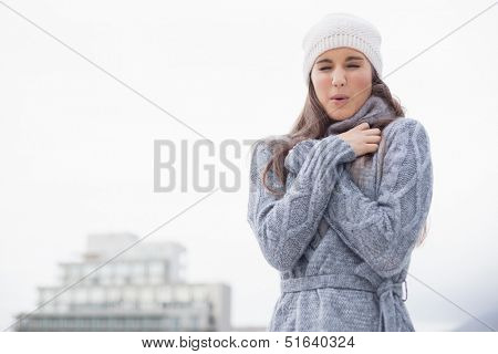 Shivering pretty woman with winter clothes on posing outdoors on a cold grey day