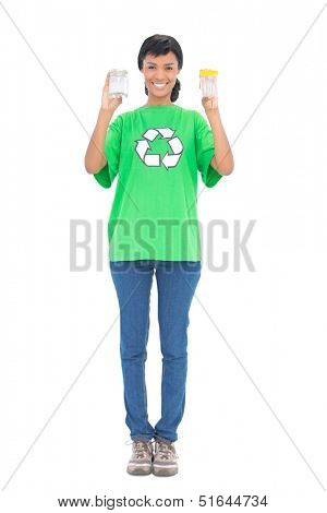 Delighted black haired ecologist holding jars on white background
