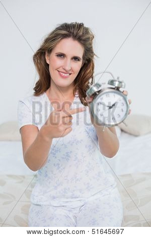 Smiling woman sitting on bed pointing at alarm clock looking at camera