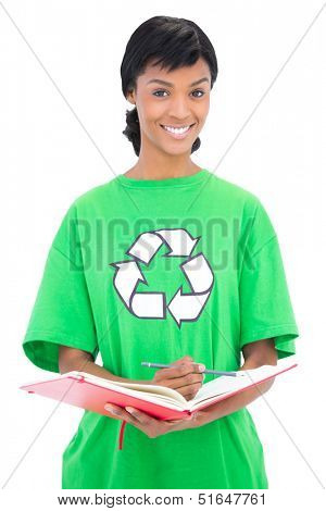 Smiling black haired ecologist checking a schedule on white background