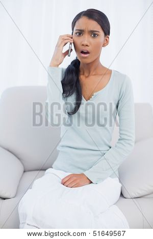 Taken aback attractive woman sitting on cosy sofa in bright living room having a phone call