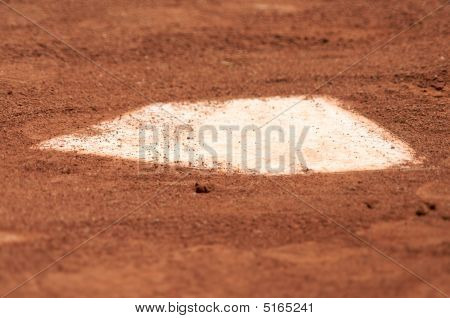 A baseball home plate is surrounded by dirt and shallow depth of field