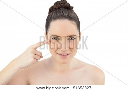 Natural model applying cream on her crows feet while posing on white background